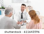 Small photo of Insurance agent showing calculator with value of benefits