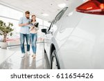 Small photo of Happy couple holding catalog and choosing car in dealership salon