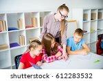 teacher helping students | Shutterstock . vector #612283532