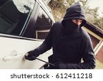 car theft - thief trying to break into the vehicle - stock photo