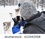 Woman Taking Photo Of Husky...