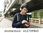 asian guy listening music by... | Shutterstock . vector #612739865