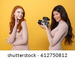 Small photo of Image of cheerful young african woman photographing redhead lady friend over yellow background.