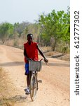 Small photo of KOUTAMMAKOU, TOGO - JAN 13, 2017: Unidentified Togolese boy in red shirt rides a bicycle in the village. Togo people suffer of poverty due to the bad economy.