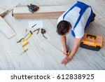 repairman laying laminate... | Shutterstock . vector #612838925