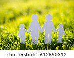 paper family on green grass... | Shutterstock . vector #612890312