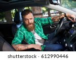 a bearded man in a new car. | Shutterstock . vector #612990446