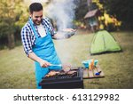 handsome man preparing barbecue ... | Shutterstock . vector #613129982