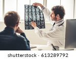 Stock photo handsome young doctor in white coat is showing x ray image to his patient while working in office 613289792
