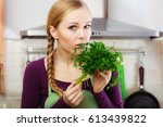 woman in kitchen holding green... | Shutterstock . vector #613439822
