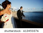 Small photo of Bride looks over her shoulder at groom standing on ocean shore