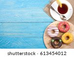 glazed donuts with a cup of tea ... | Shutterstock . vector #613454012