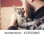 Stock photo close up of handsome young man who is standing on a balcony with his cat home pets beard man in 613531865