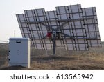 Small photo of Back view of solar panel: turning gear for tracking the sun and correct orientation, red inverter to transform direct current into alternate and direct/alternate current cabinet.