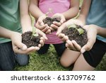 hands holding sapling in soil... | Shutterstock . vector #613709762