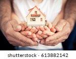family holding house in hands.... | Shutterstock . vector #613882142