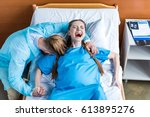 Small photo of pregnant woman giving birth in hospital while man hugging her