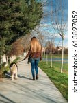 Stock photo a girl is walking with a dog along the embankment beautiful husky dog the river spring 613897052