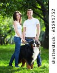 Stock photo young couple walking with dog in park 61391752