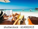 woman on sunbed reading book... | Shutterstock . vector #614002415