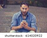 shocked upset young man looking ... | Shutterstock . vector #614020922
