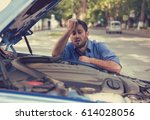 Small photo of young stressed man having trouble with his broken car looking in frustration at failed engine