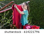girl is hanging the washed red... | Shutterstock . vector #614221796