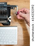 Small photo of Conceptual composition, a female hand turning the handle of an old retro adding machine on a background of modern computer keyboard