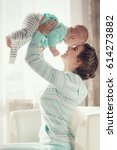 young mother holding her... | Shutterstock . vector #614273882