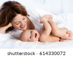 mother and child on a white bed.... | Shutterstock . vector #614330072