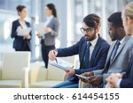 young co workers discussing... | Shutterstock . vector #614454155