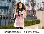Small photo of Happy woman in coat holding cup of coffee and listening music while standing on the street and looking away