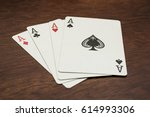 Small photo of four aces on a wooden table with the ace of spades on top