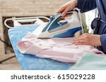 woman working with handy iron | Shutterstock . vector #615029228