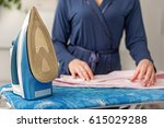 caring wife using modern iron | Shutterstock . vector #615029288