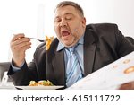 Small photo of Hardworking tireless employee working a eating at the same time