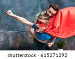 Small photo of father holding son in superhero costume flying at home