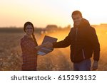Small photo of Woman engineer with laptop and landowner shaking hands on field at sunset with tractor working in background. Agribusiness concept