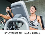 Small photo of Low angle portrait of beautiful sportive brunette woman exercising using elliptical machine next to fit man, both smiling during workout in modern gym