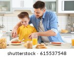 dad and son having lunch at home | Shutterstock . vector #615537548
