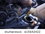 motor oil pouring to car engine. | Shutterstock . vector #615642422