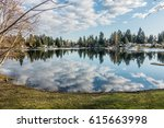 Homes, trees and sky are reflected in the water of Mirror Lake in Federal Way, Washington.