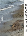 Small photo of Beach of Timmendorfer Strand with sand and gravel, some footprints close to the low, foamy surge; allover closeup, Timmendorfer Strand, Germany, 10/2013