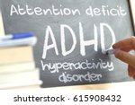 Small photo of Hand writing on a blackboard in a class with the word ADHD written on. Some books and school materials.Attention Deficit Hyperactivity disorder concept.