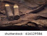Small photo of group of cigars on tobacco leaves