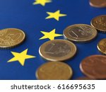Euro coins (EUR), currency of European Union over flag of Europe - stock photo