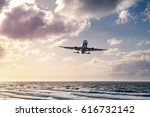 plane flying in over sea during ... | Shutterstock . vector #616732142
