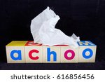 "Small photo of ""ACHOO!"" Flu and cold concept with tissue against black background."