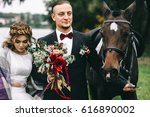 young couple with a black horse ... | Shutterstock . vector #616890002