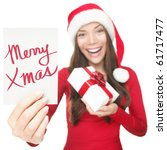 Christmas woman showing blank sign with empty copy space. Beautiful young smiling woman in Santa hat holding white paper card sign. Caucasian / Asian model isolated on white background. Shallow DOF. - stock photo